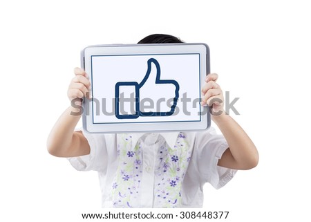 Little girl standing in the studio while holding a digital tablet and showing a thumb up sign on the screen - stock photo