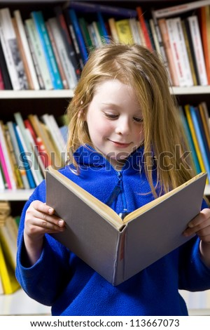 Little girl standing near the bookshelf - stock photo