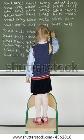 Little girl standing on chair in front of blackboard. Writing on it. Rear view, whole body - stock photo