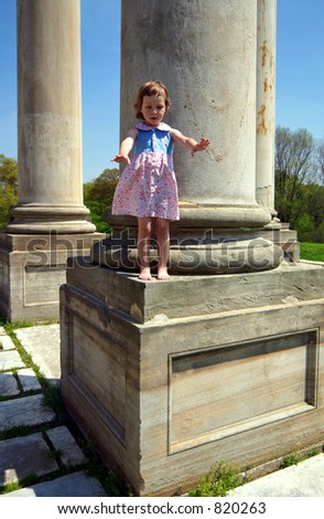 Little girl standing on the column - stock photo