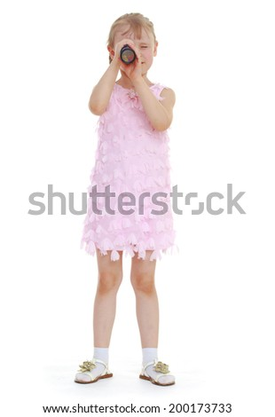 little girl stands at full height, and looked through a telescope. Isolated on white background - stock photo