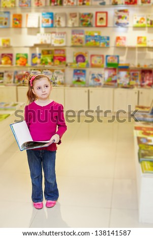 Little girl stands looking thoughtful holding open book in book department at store - stock photo