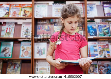 Little girl stands reading book in the hall of library with many bookshelves. - stock photo