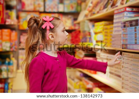 Little girl stretches to shelf with table games in book department of store - stock photo