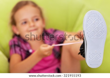 Little girl struggling to tie her shoes - focus on foot, copy space - stock photo