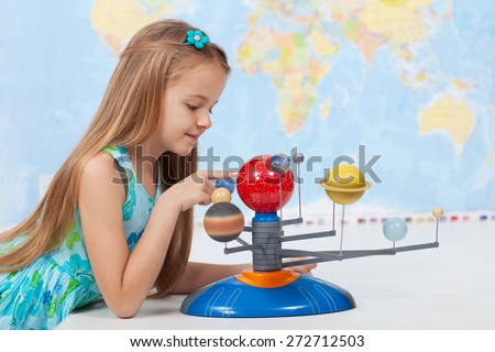 Little girl studies the solar system in geography class - looking at the scale model of planets - stock photo