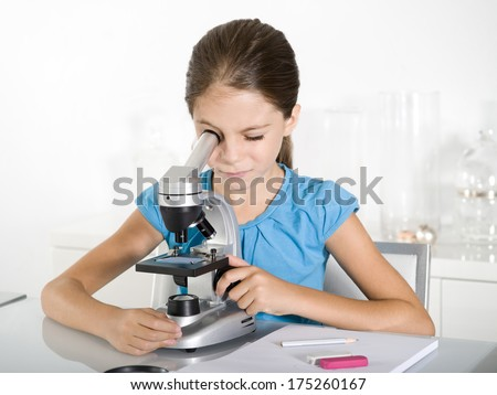 little girl  study with microscope - stock photo