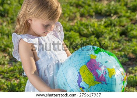 Little girl studying world globe outdoors. - stock photo