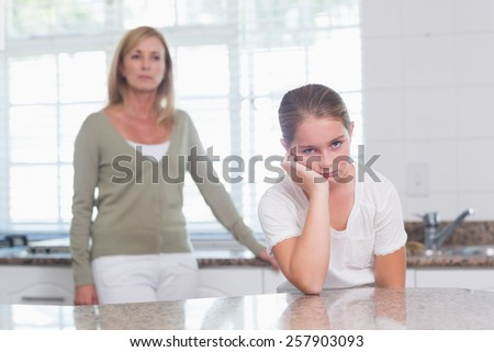 Little girl sulking after am argument with her mother at home in the kitchen - stock photo