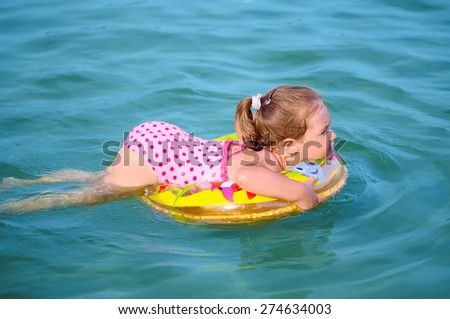 Little girl swimming on the lake - stock photo
