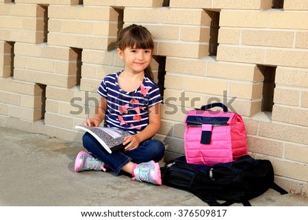 Little girl takes a break from her school work - stock photo