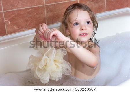 little girl taking a bath with foam - stock photo