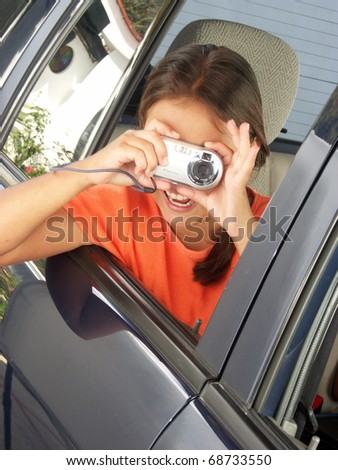 Little girl taking a picture out from a car window. - stock photo