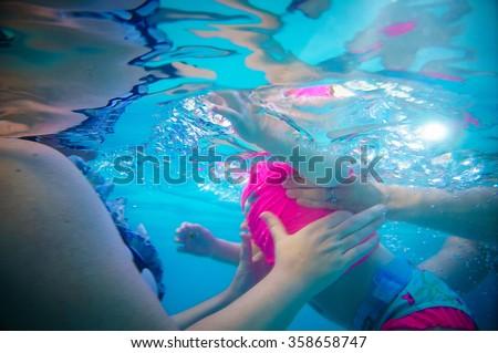 Little girl taking swimming lessons - stock photo