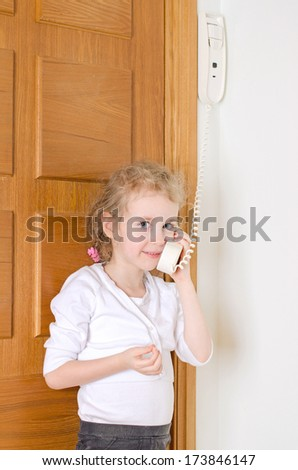 Little girl talking on the intercom at home. - stock photo