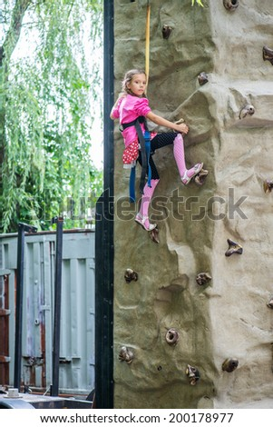 Little girl talking trains on climbing wall in summer city Park.. - stock photo