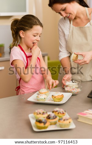 Little girl taste sprinkles decorating cupcakes with mother at home - stock photo