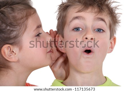 little girl telling his brother a secret - stock photo