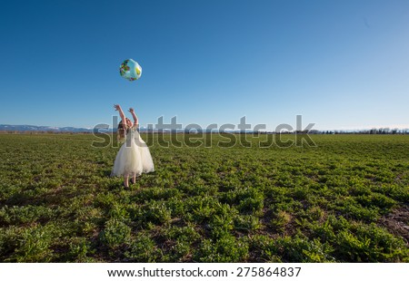 Little girl throwing a globe in the air while standing in a large hay field. - stock photo