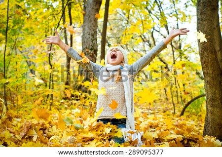 little girl throwing autumn leaves - stock photo