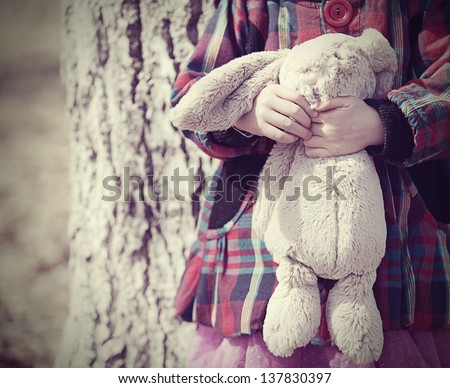 Little girl toddler holding a stuffed bunny toy - stock photo
