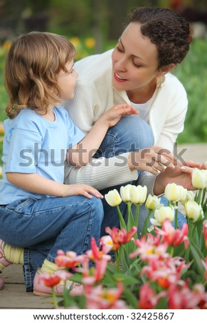 little girl together with mother sits at bed with tulips - stock photo
