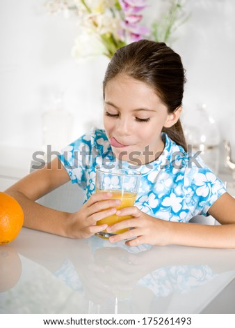 little girl tongue out looking orange juice - stock photo