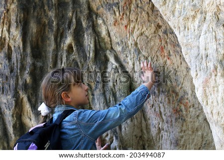 little girl touch a granite rock outdoors - stock photo