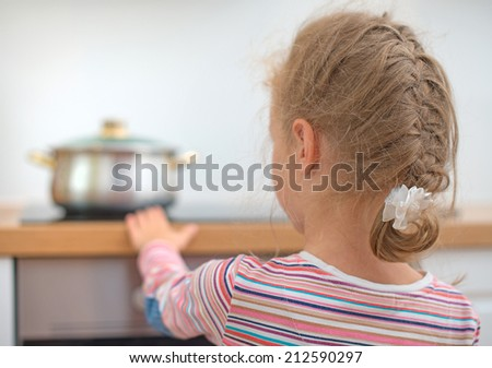 Little girl touches hot pan on the stove. Dangerous situation at home.  - stock photo