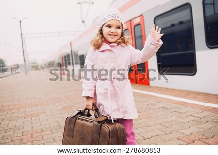 Little girl traveling with her baggage - stock photo