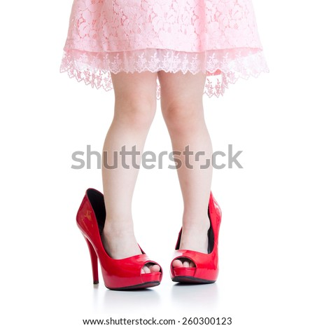 Little girl trying her mother's shoes on the floor - isolated - stock photo