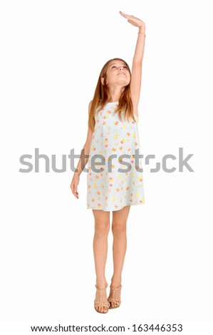 little girl trying to be taller isolated in white - stock photo
