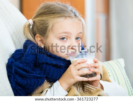 Little girl under blanket with warm milk and fever indoors