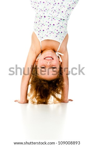little girl upside down on a white background - stock photo