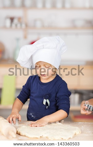 Little girl using cutter on dough at kitchen counter - stock photo