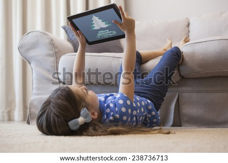 Little girl using digital tablet in the living room against merry christmas message - stock photo