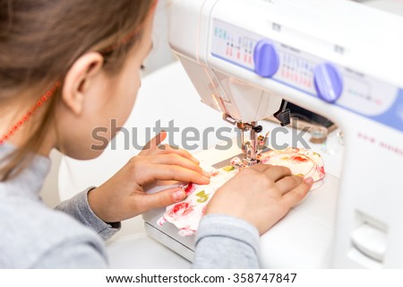 Little girl using sewing machine to make crafts - stock photo