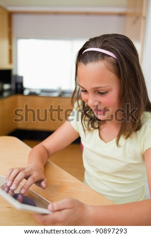 Little girl using tablet at the kitchen table - stock photo