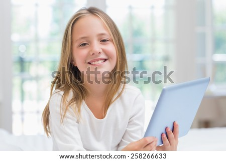 Little girl using tablet pc sitting on her bed at home in the bedroom - stock photo