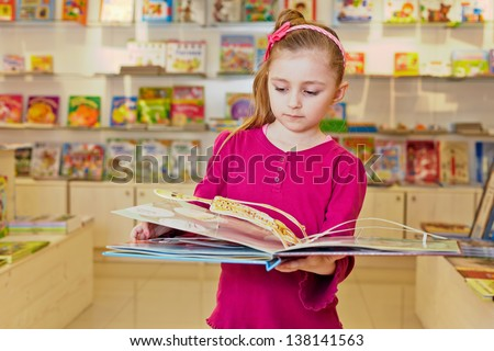 Little girl views fold-out book on anatomy in book department at store - stock photo