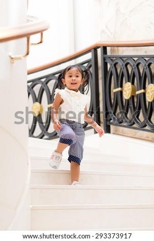 Little girl walking downstair - stock photo