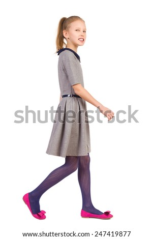 Little girl walking in gray dress and looking at camera. Full length length studio shot isolated on white. - stock photo