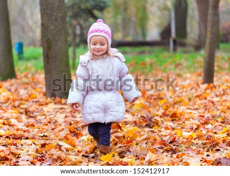 Little girl walking in the autumn park - stock photo