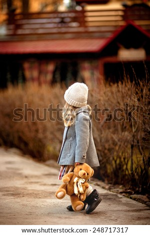 little girl walking in the garden with a teddy bear in her hand - stock photo