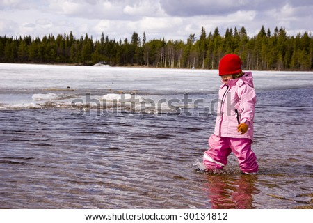 little girl walking in the lake and think it's really fun - stock photo