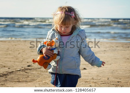 little girl walks on a beach with a toy - stock photo