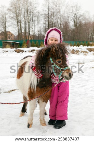 Little girl walks with mini horse in winter day - stock photo