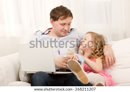 Little girl wants to play with dad. Father working with computer, but he giving attention to his daughter - stock photo