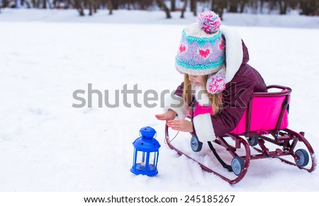 Little girl warms her hands on candle in the lantern outdoors - stock photo