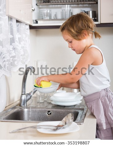 little girl washing dishes in the kitchen - stock photo